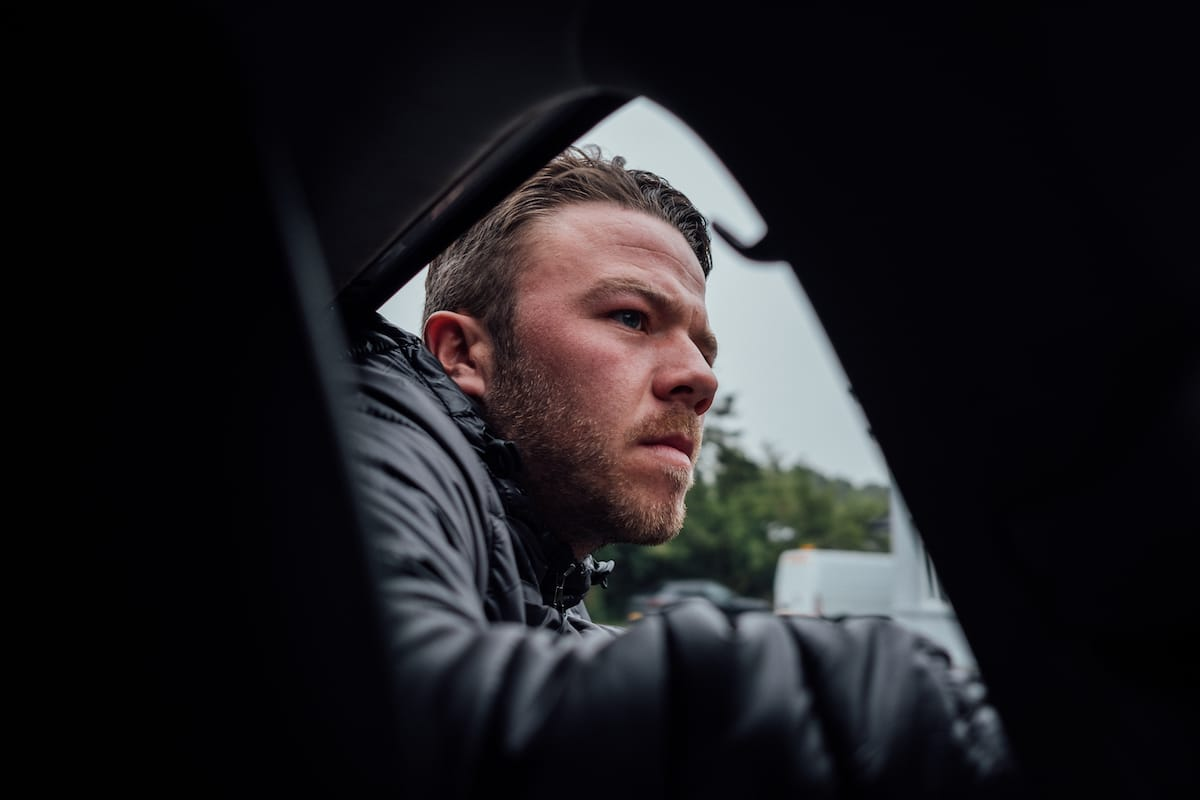A view from the font passenger seat of a Neutral Service race support vehicle showing mechanic Adam Johnson leaning out of a rear window