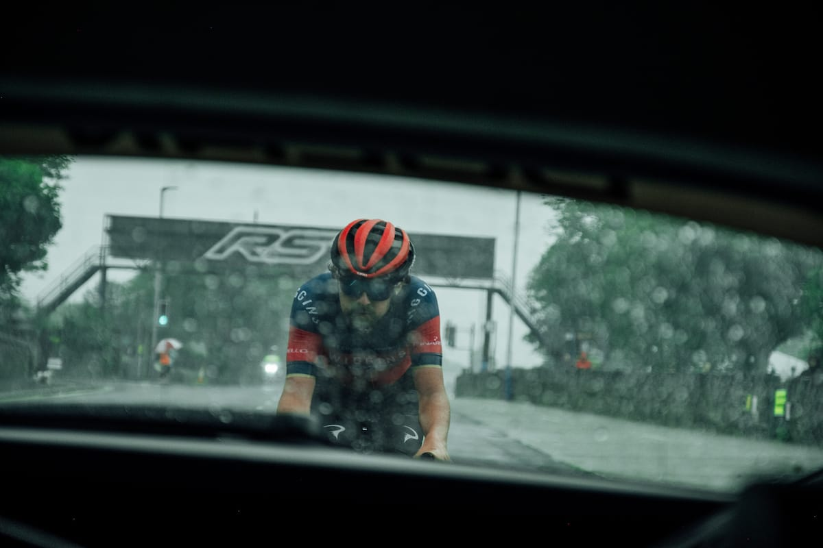 A view of cyclist Ben Healy through the rear window of a Neutral Service race support vehicle as he's riding behind
