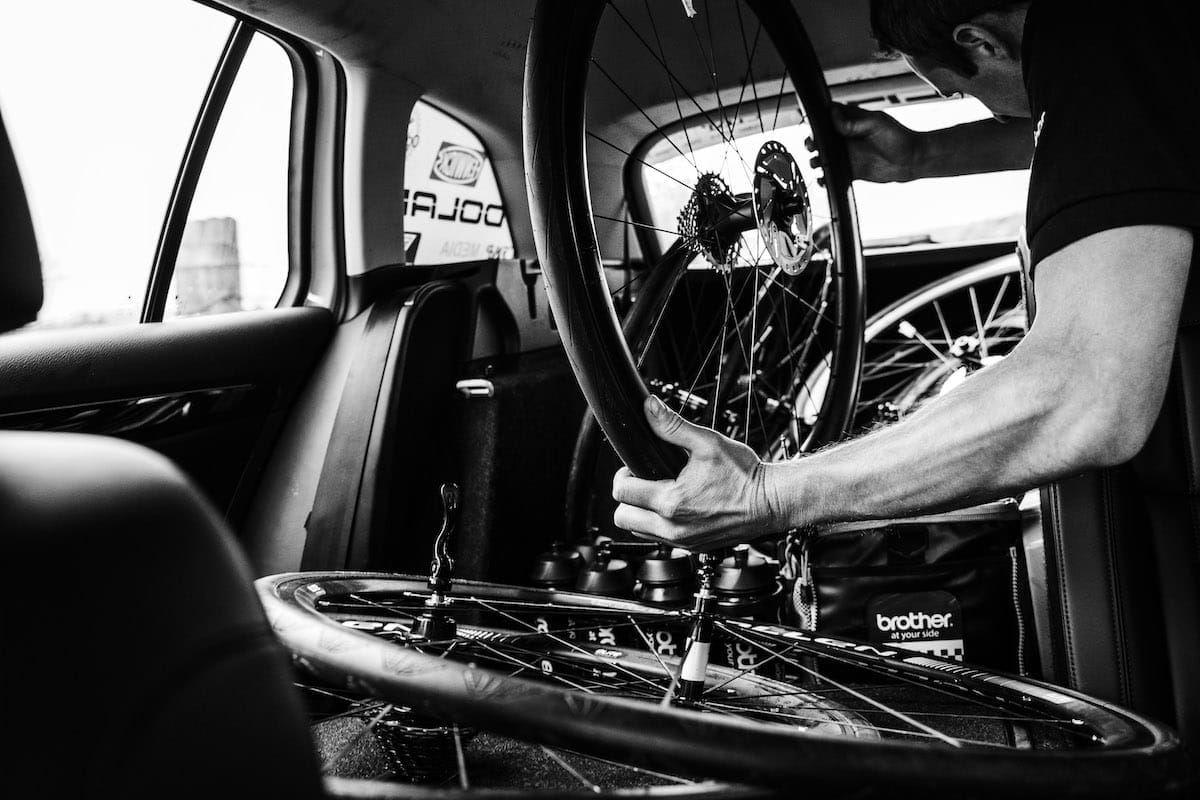 A member of the Neutral Service support crew holding a bike disc wheel in the back of a race support vehicle