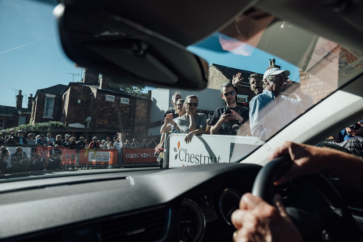 A view from the front passenger seat of a Neutral Service race support vehicle as it drives past spectators at the Lincoln Grand Prix