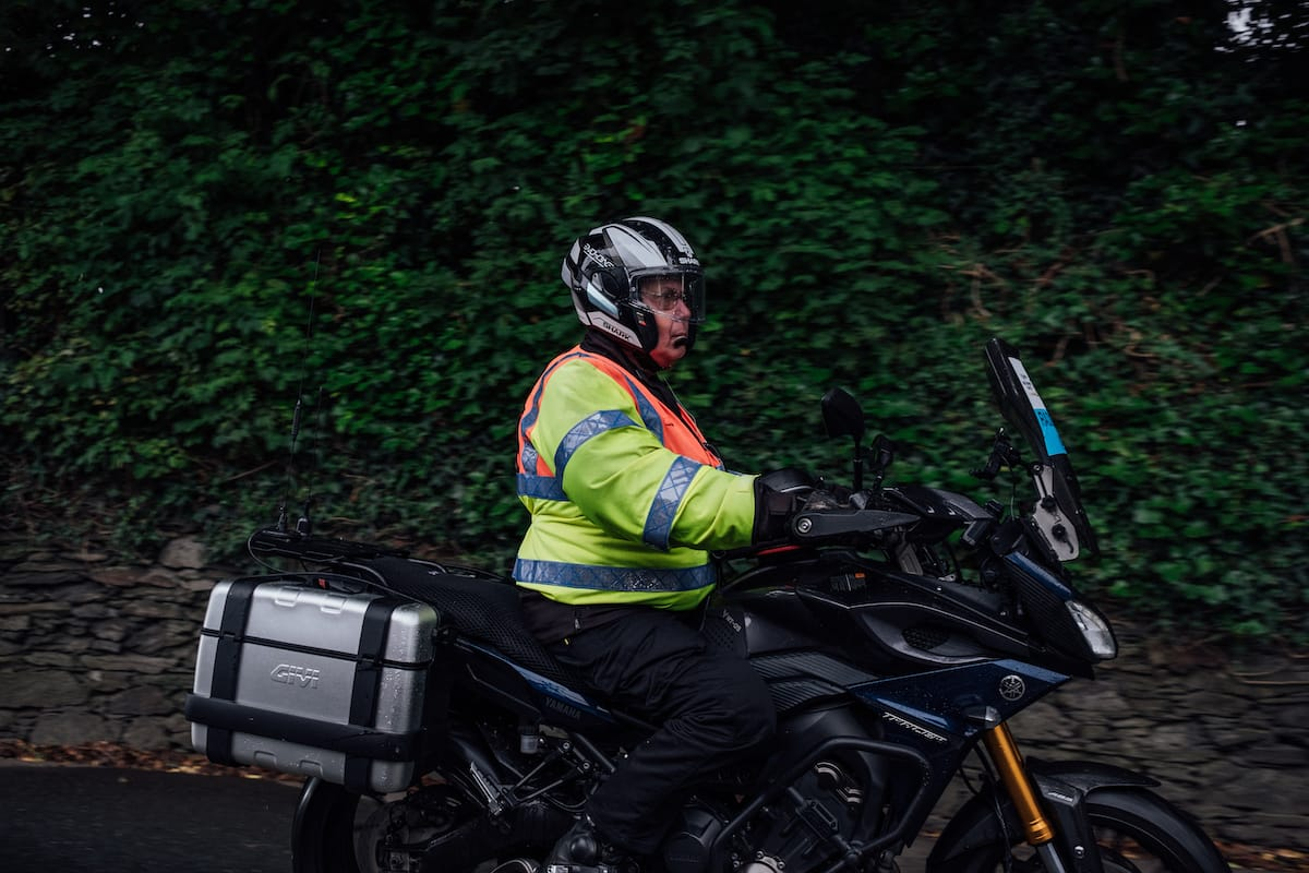 Side view of a motorcyclist wearing a high visibility jacket as he's riding past