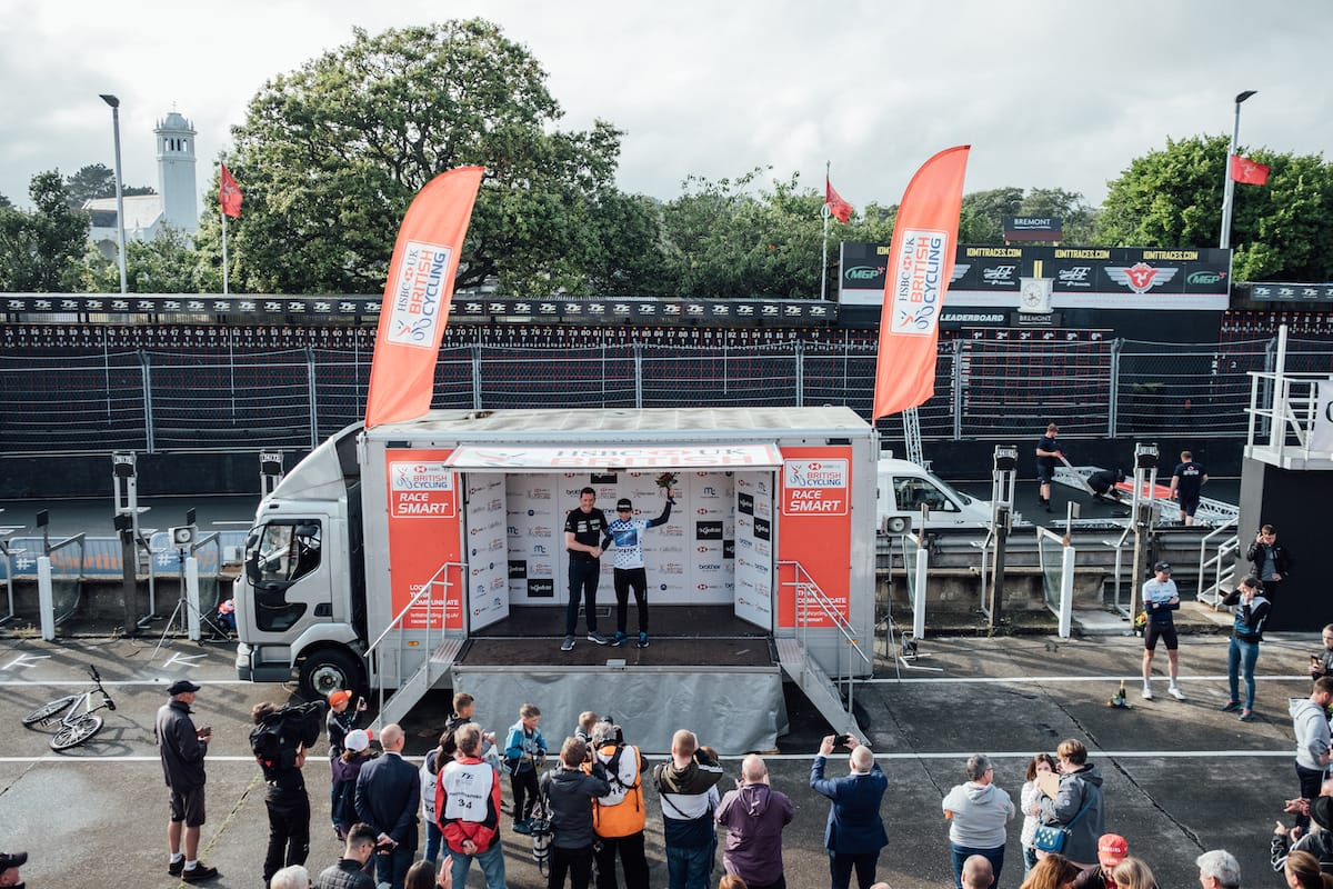 A crowd gathered around a podium built into an open sided truck where a cyclist receives an award at the HSBC National Road Series