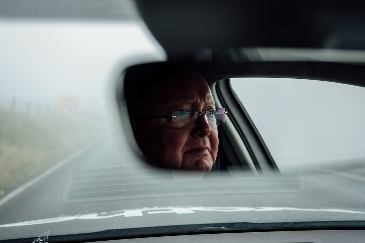 Tony Barry seen through the rear view mirror of a Neutral Service race support vehicle