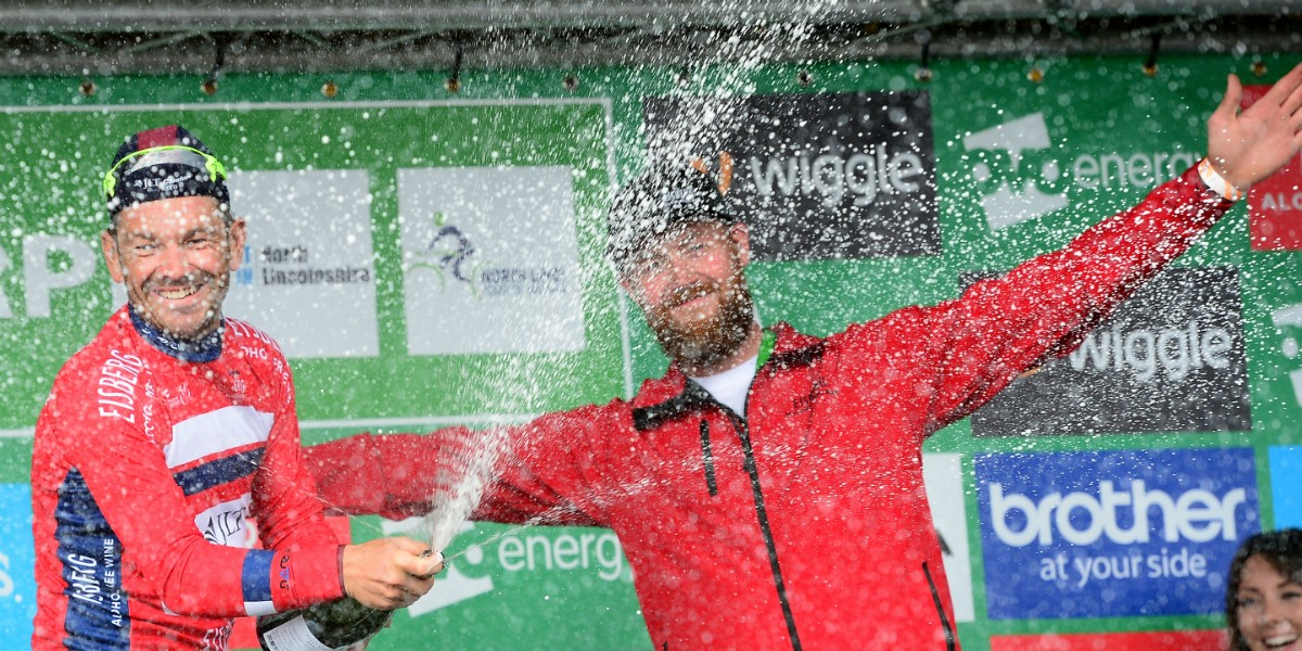 cyclist celebrates victory with champagne on the podium
