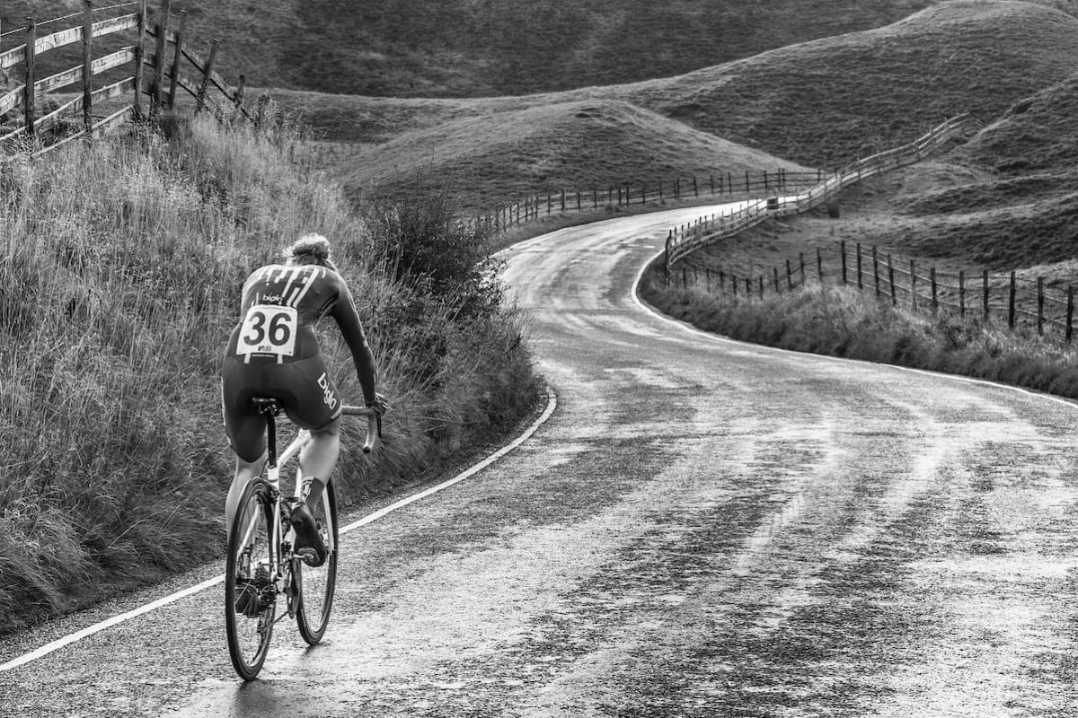 Cyclist Lizzie Banks riding down a winding hilly road