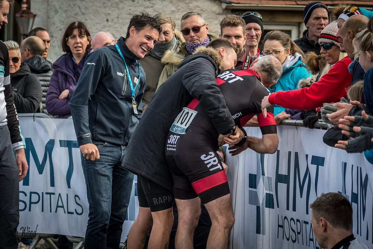 The team assisting an exhausted cyclist who is greeting spectators after a hill climb
