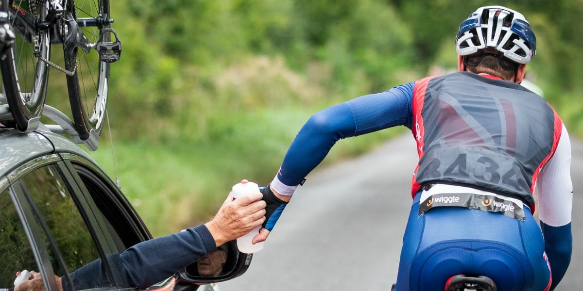 cyclist takes on water from support vehicle