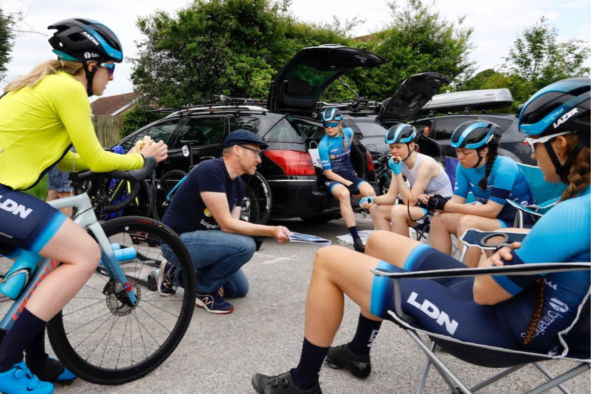 General manager Ian Watson of Team Brother UK-LDN kneeling while giving team talk to cyclists in car park