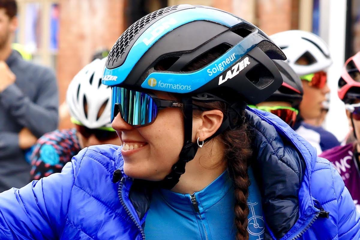 Closeup of Amy Marks smiling to someone out of shot while wearing sunglasses and a helmet with other cyclists in the background