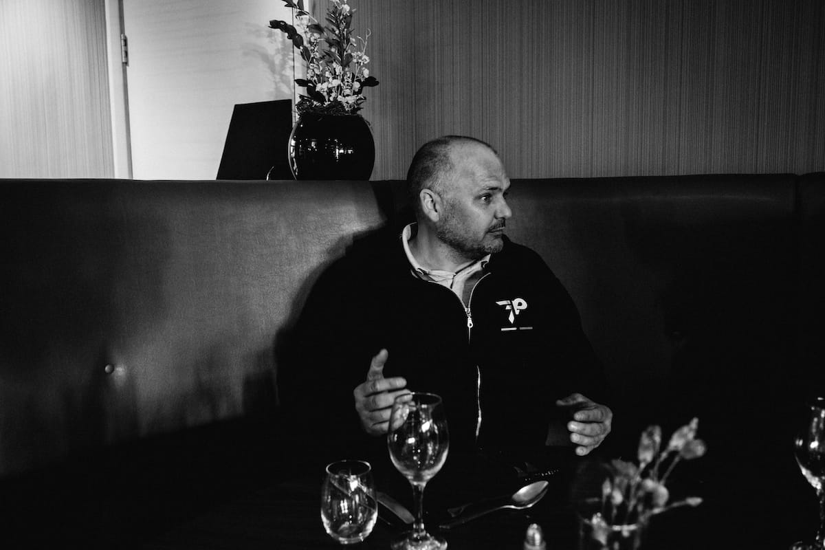Simon Howes gesturing while talking to someone who is out of shot while sat on a corner sofa with empty wine glasses in the foreground
