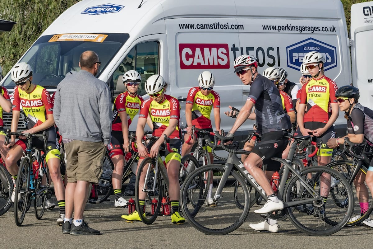 Chartered psychologist Peter Hudson advising the CAMS-Tifosi team who are straddling their bikes in front of a support vehicle
