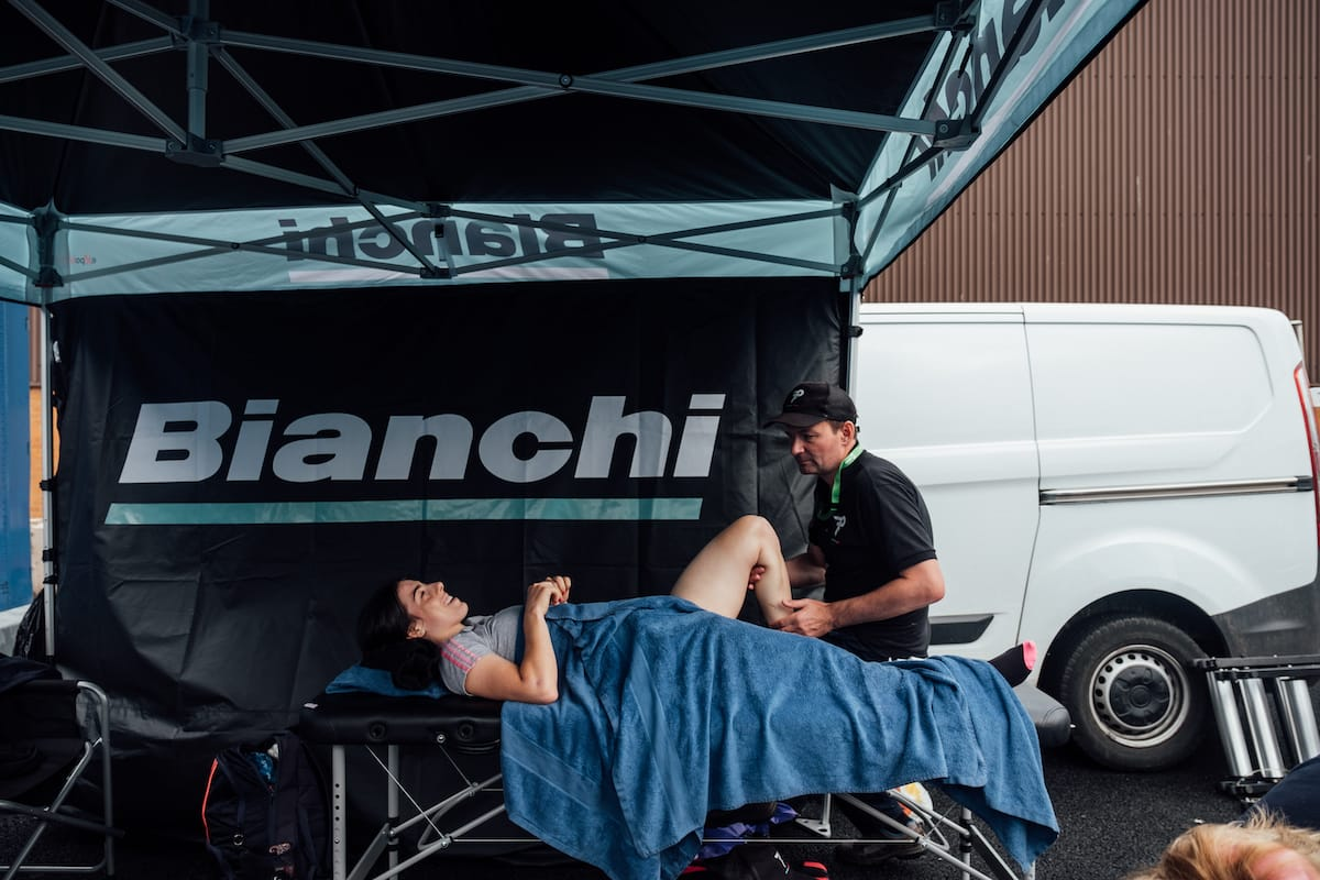 Soigneur Phil Holloway helping a cyclist warm up while they are lying on a treatment table under a Bianchi branded gazebo