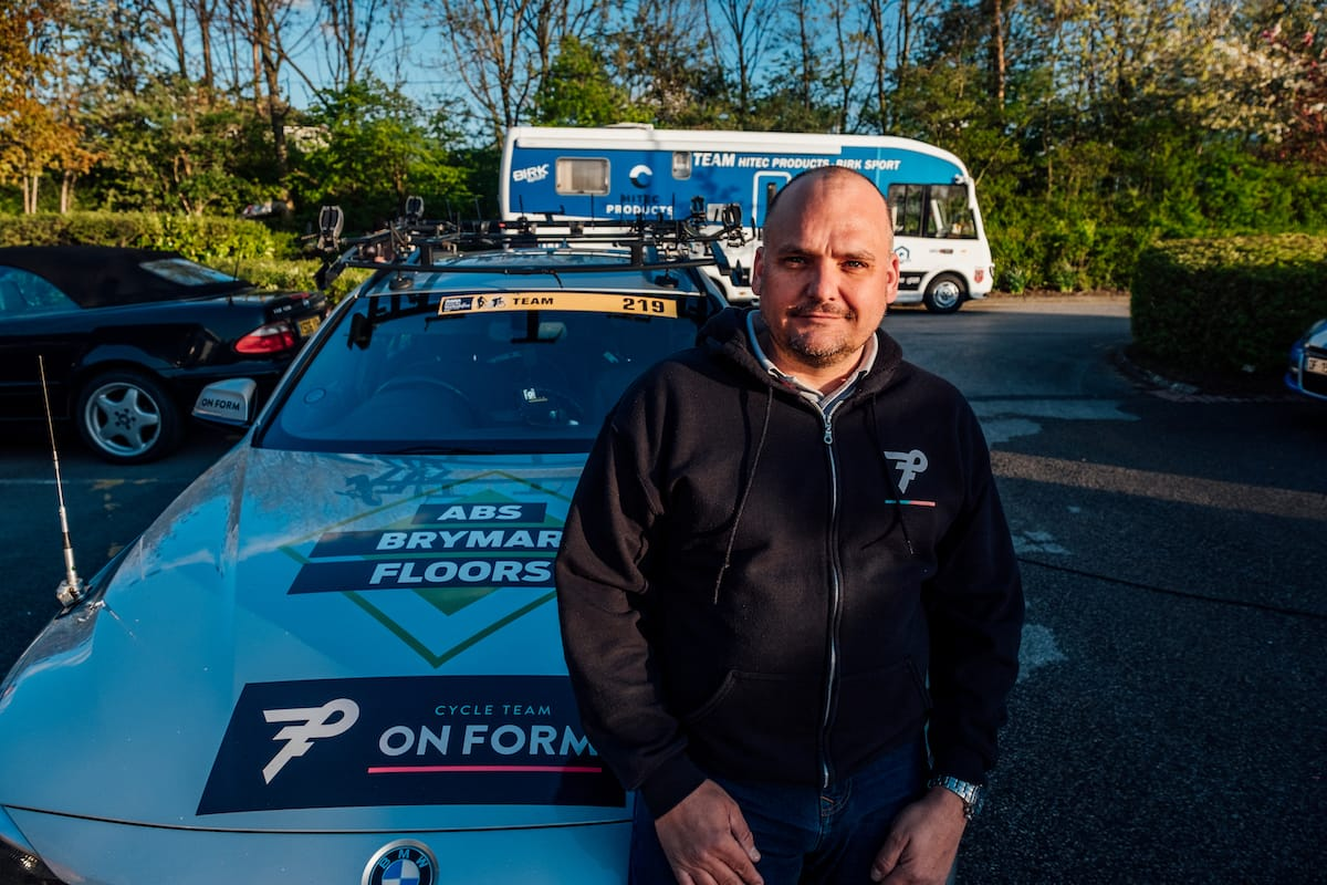 Simon Howes sat on the bonnet of a OnForm support vehicle in a car park with other vehicles in the background