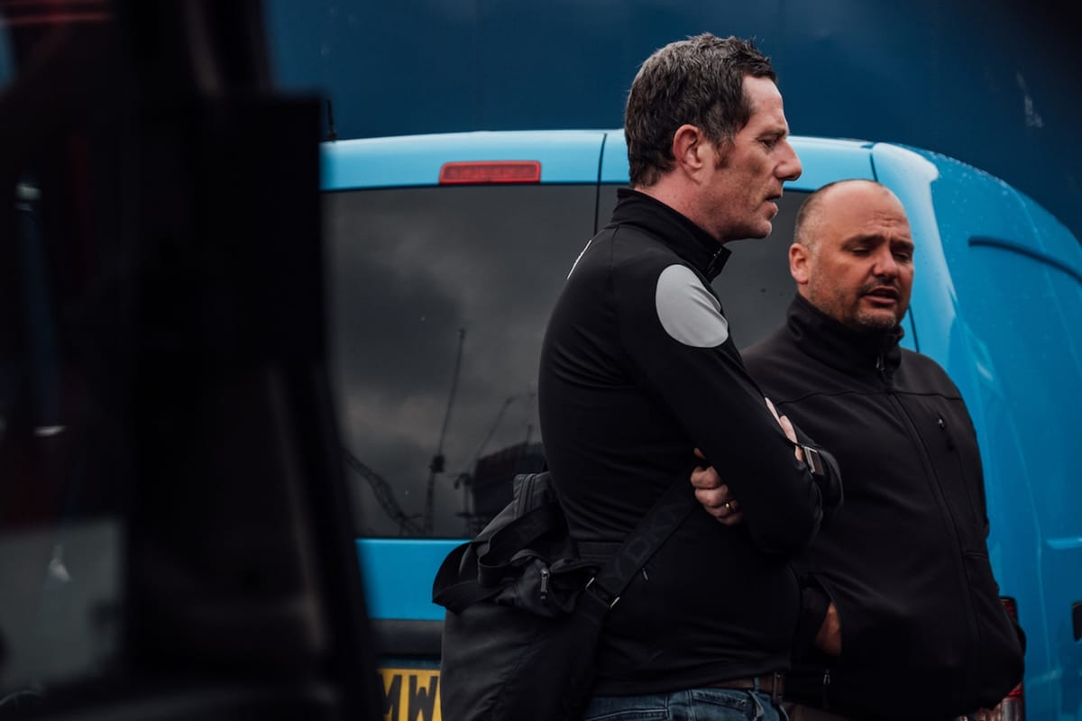 Side shot of Phil Jones MBE and Simon Howes as they are talking while stood in front of a blue van