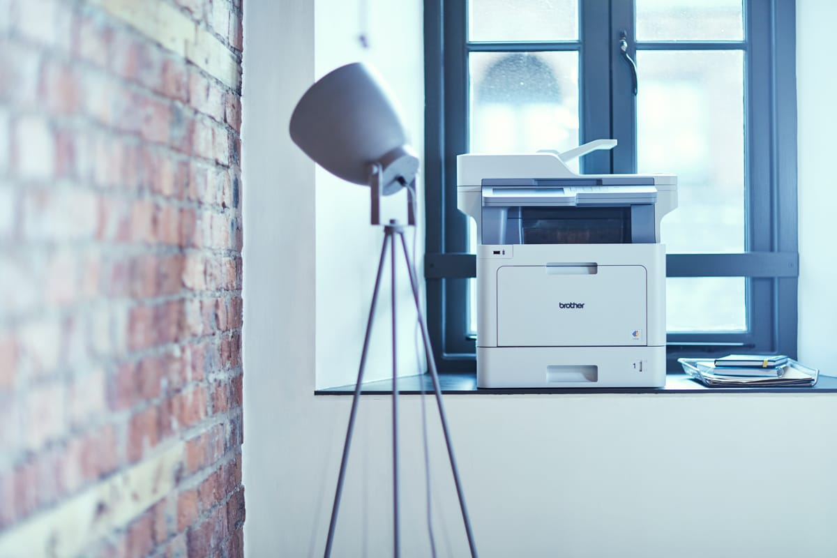 Brother MFC colour laser printer on a window ledge next to a tripod floor lamp