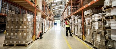 A woman in a high visibility jacket working in a warehouse full of boxes