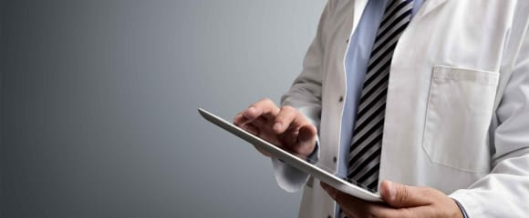 Close-up of doctor wearing white coat entering information into a tablet device