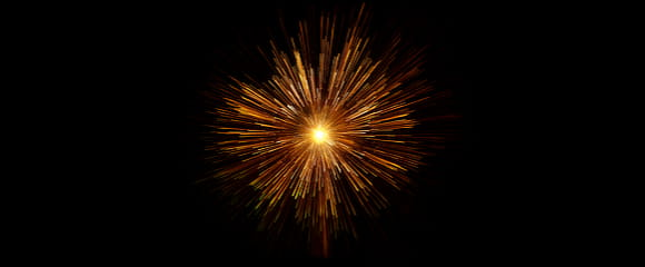 Orange firework exploding on a black background