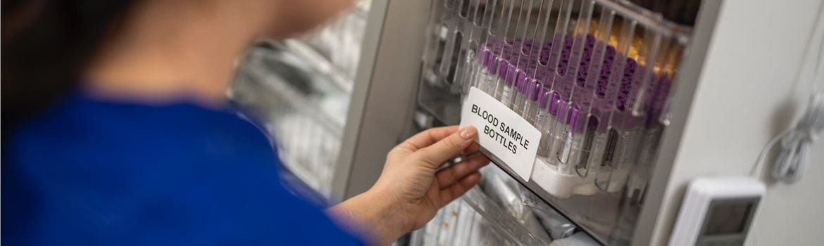 A female lab technician applying a printed label to blood sample bottles