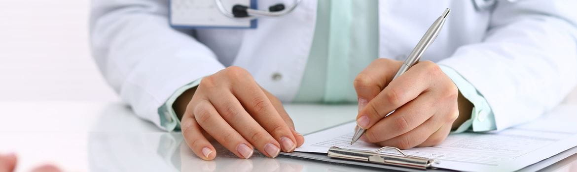 Close-up of a female doctor writing patient notes on a clipboard