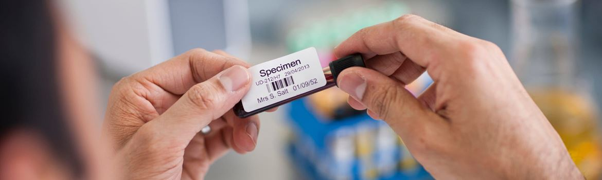 A male healthcare professional in a laboratory applying a barcode label to a test tube containing a blood sample, labelled 'Specimen'