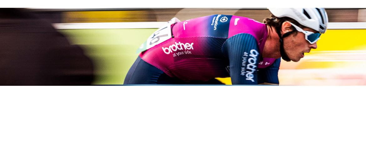 Cyclist from Brother UK backed, Crimson Performance team, riding past spectators in a blur