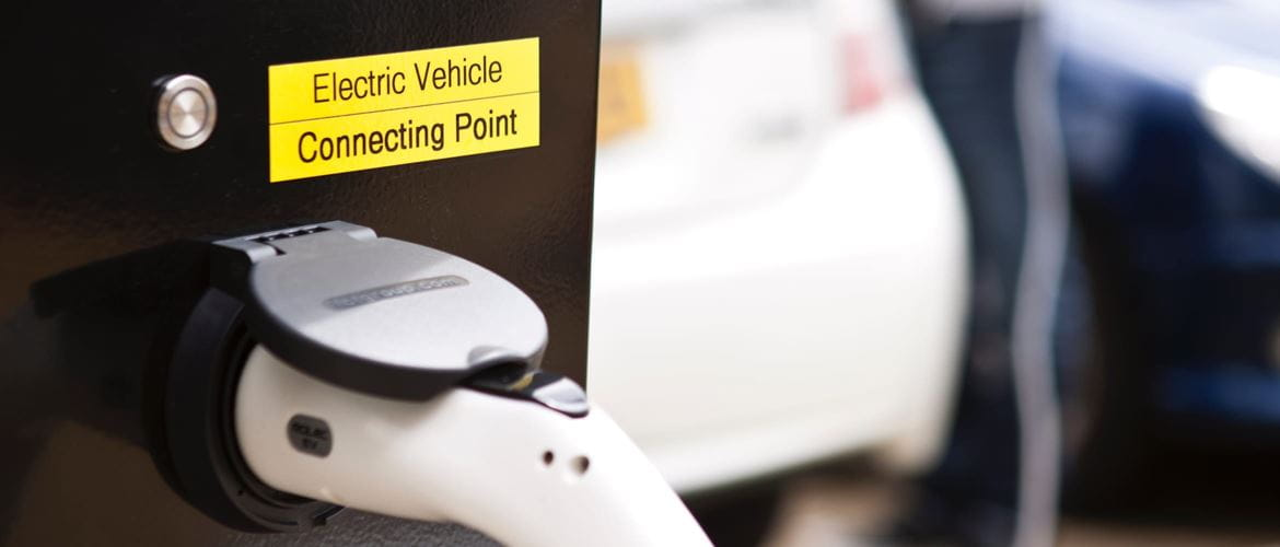 Close-up of an electric vehicle connecting point with vehicle and owner in the background