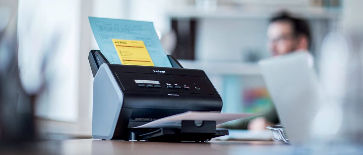 Brother ADS-2400 multiple page scanner on a desk in an office environment