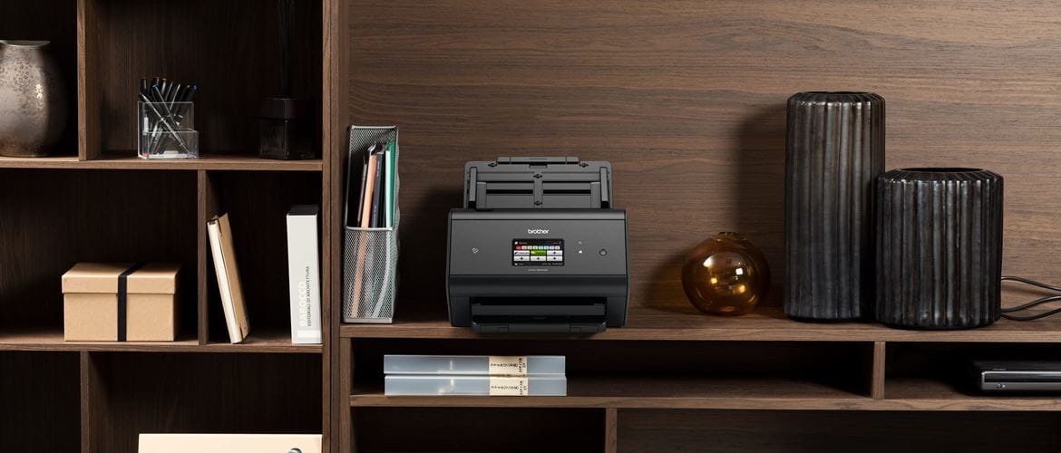 Brother ADS-3600W secure scanner on a dark wood shelving unit with a mixture of office and decorative items