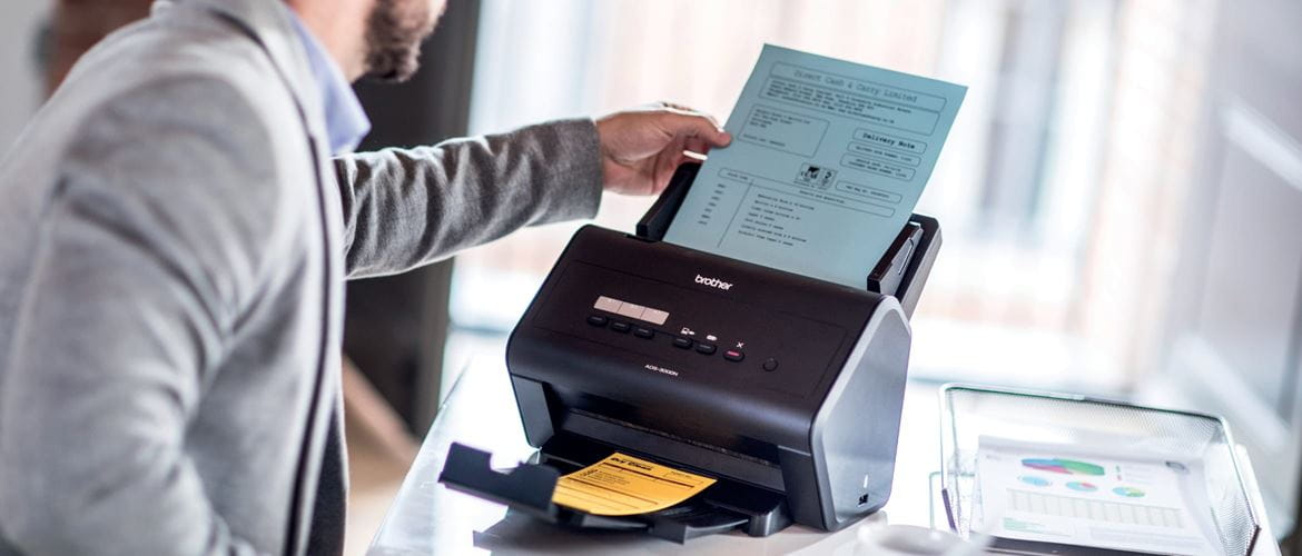 Man adding a document to the input tray of a Brother ADS-3000N sheetfed desktop scanner in a home office environment
