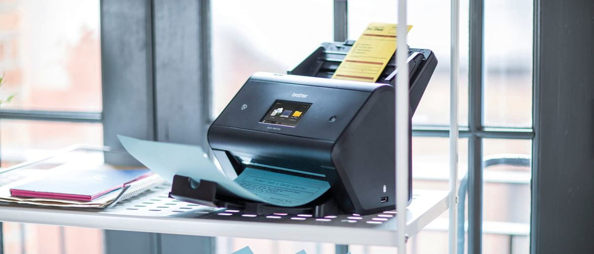 Brother ADS-3600W wireless scanner on a metal frame shelving unit in front of double glass doors