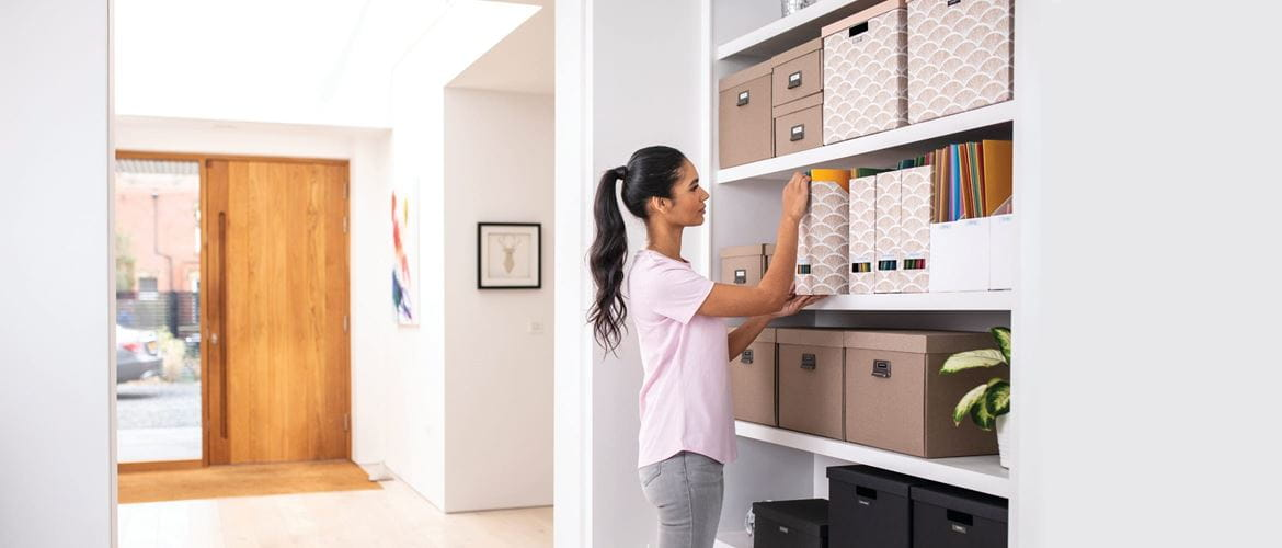 A lady pulling a labelled box file from a bookshelf in a home office environment
