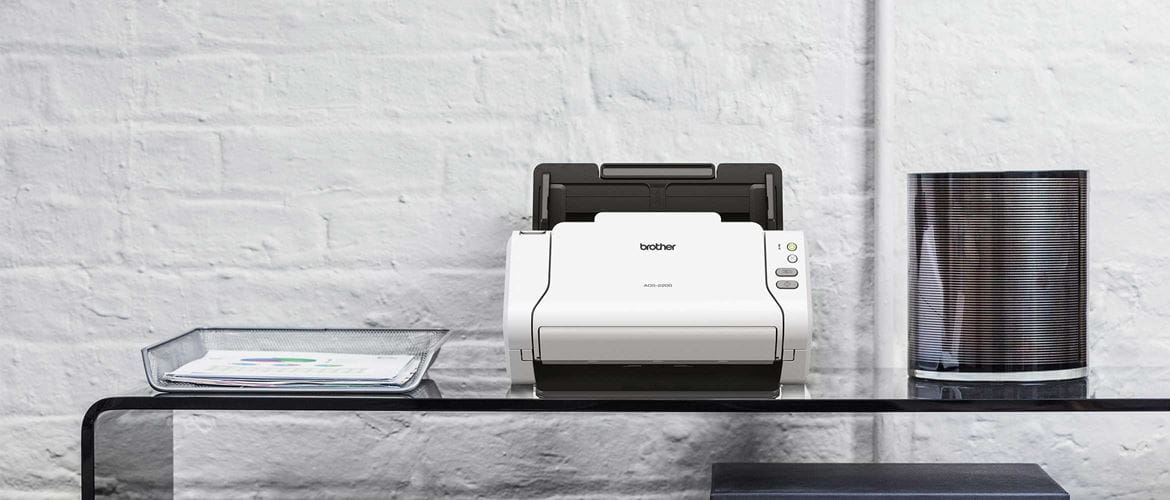 Brother ADS-2200 desktop scanner on glass table with curved edge, wire paper tray