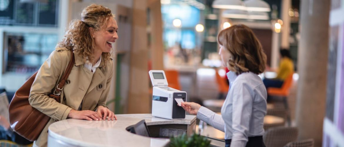 Female sales assistant serving woman at retail checkout