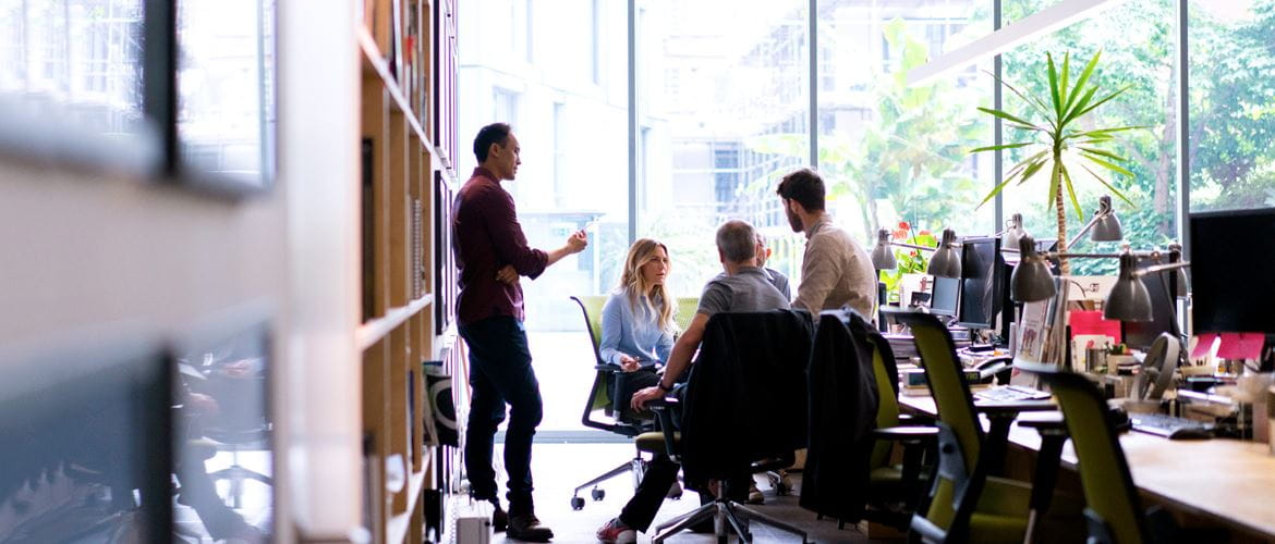Four co-workers are informally collaborating in a brightly lit workplace of the future,