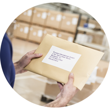 a warehouse employee holding an envelope with a printed label