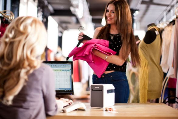Woman in clothes store purchasing pink clothes and receipt being printed on Brother TD-2000 label printer