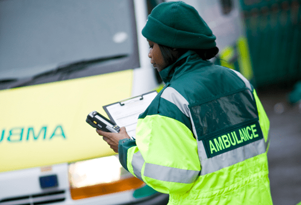 An emergency worker looking at a mobile device with an ambulance in the background