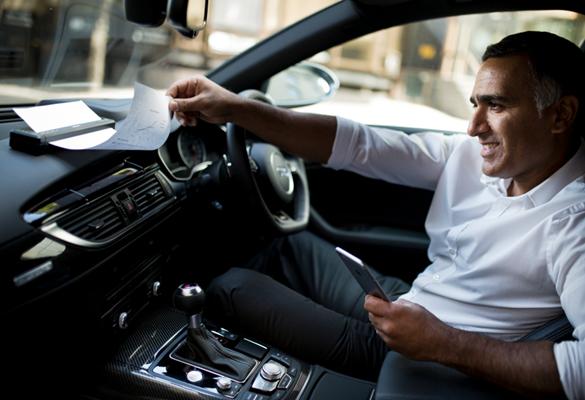 A businessman looking through paperwork on a car dashboard