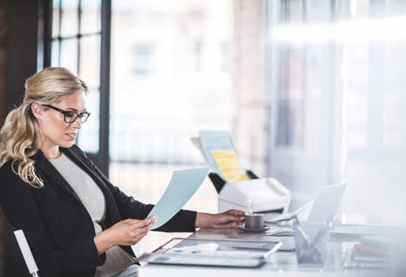 A business woman reading a document while sitting at a desk with a scanner to her side in an office environment