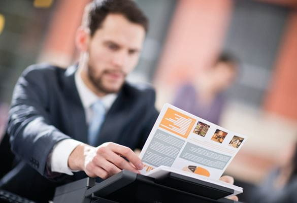 A businessman using a professional Brother desktop scanner to scan a double-sided document
