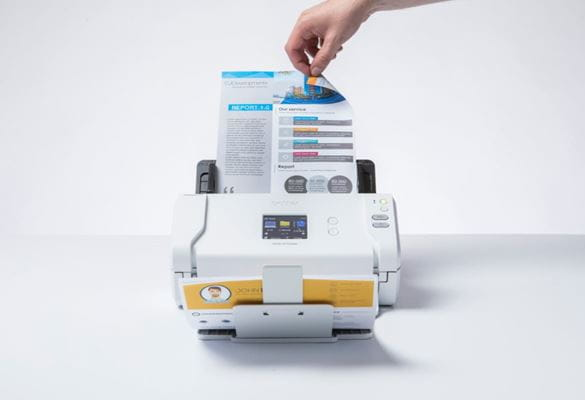 A person who is out of shot turning the page of a double-sided document in the input tray of Brother ADS-2700W sheetfed scanner