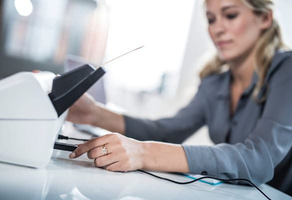 A business woman inserting a USB flash drive into the rear of a Brother ADS-2700 multiple page scanner