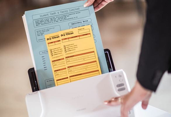 Close-up of a lady using a Brother sheetfed scanner to scan multiple documents