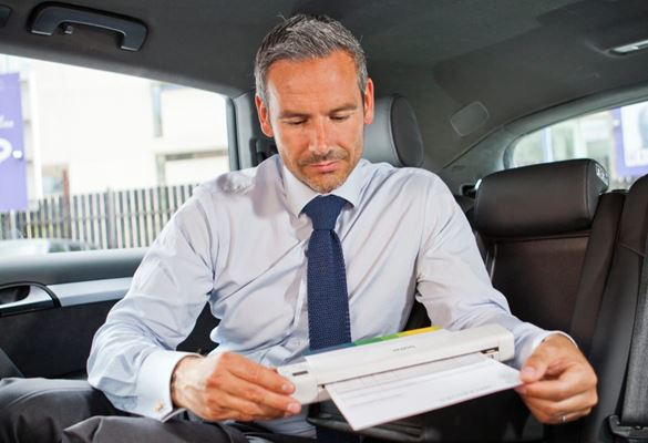 A businessman using a portable wireless scanner while sat in the back seat of a stationary vehicle