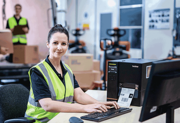 female employee using a brother TJ industrial label printer in a warehouse setting