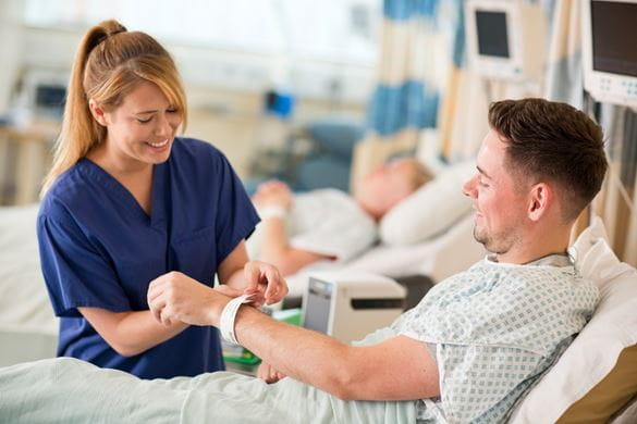 Nurse fastening a wristband to a patient lying in a hospital bed