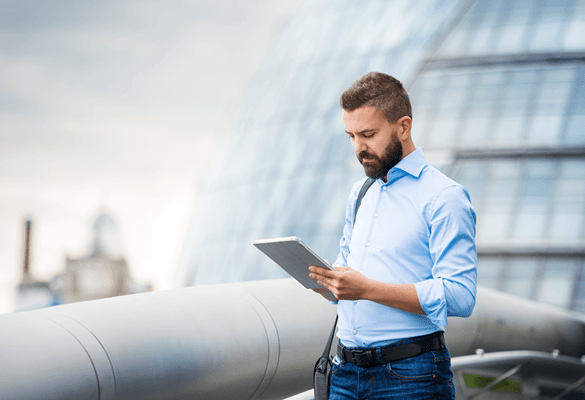 A businessman looking at a tablet device while standing on an office rooftop terrace