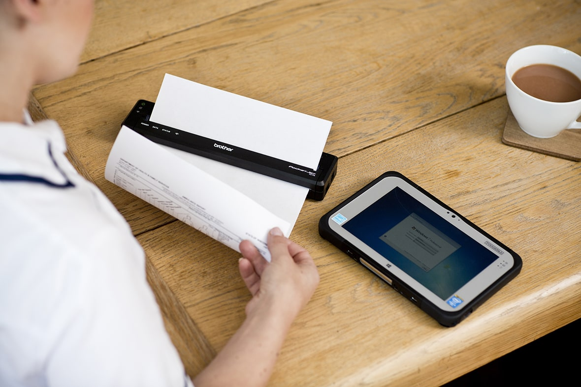 Woman printing a document from a tablet device to a Brother mobile printer