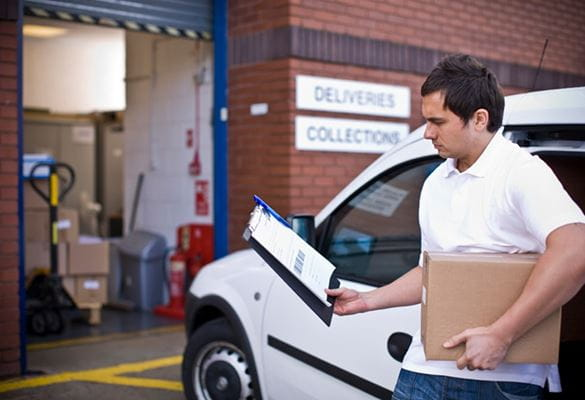 Courier reviewing delivery information on a clipboard before delivering parcel